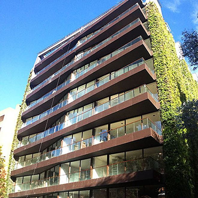 Balconies of the building with vertical gardens visible on the side