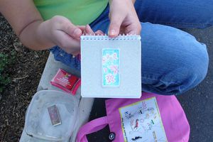 A young girl shows off her letterboxing kit