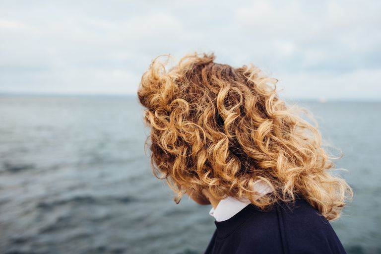 A curly haired redhead stands in front of water.