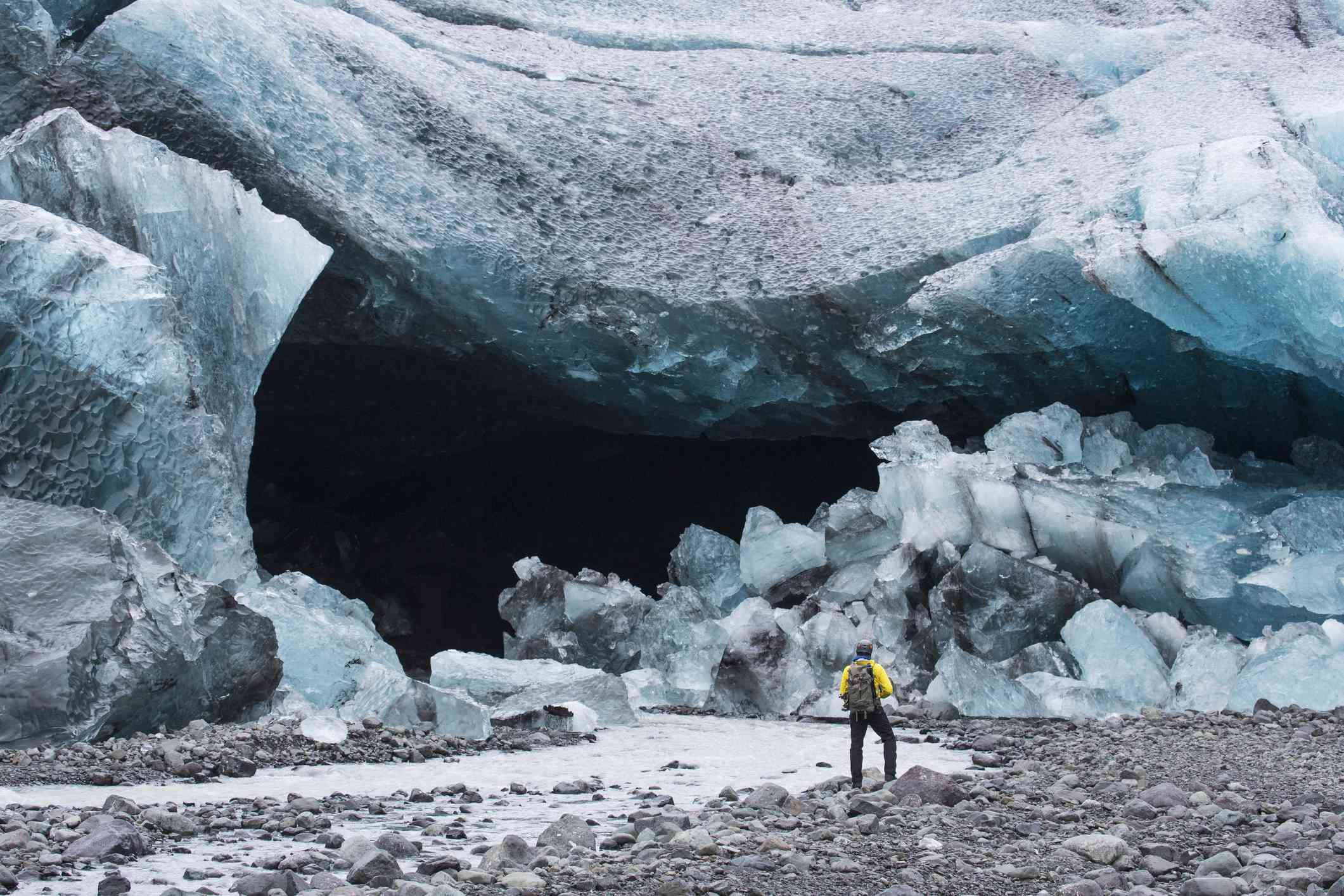 Person standing at the entrance to an ice cave