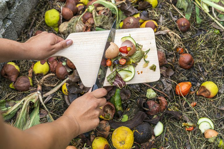 Woman scraping food scraps onto a compost pile
