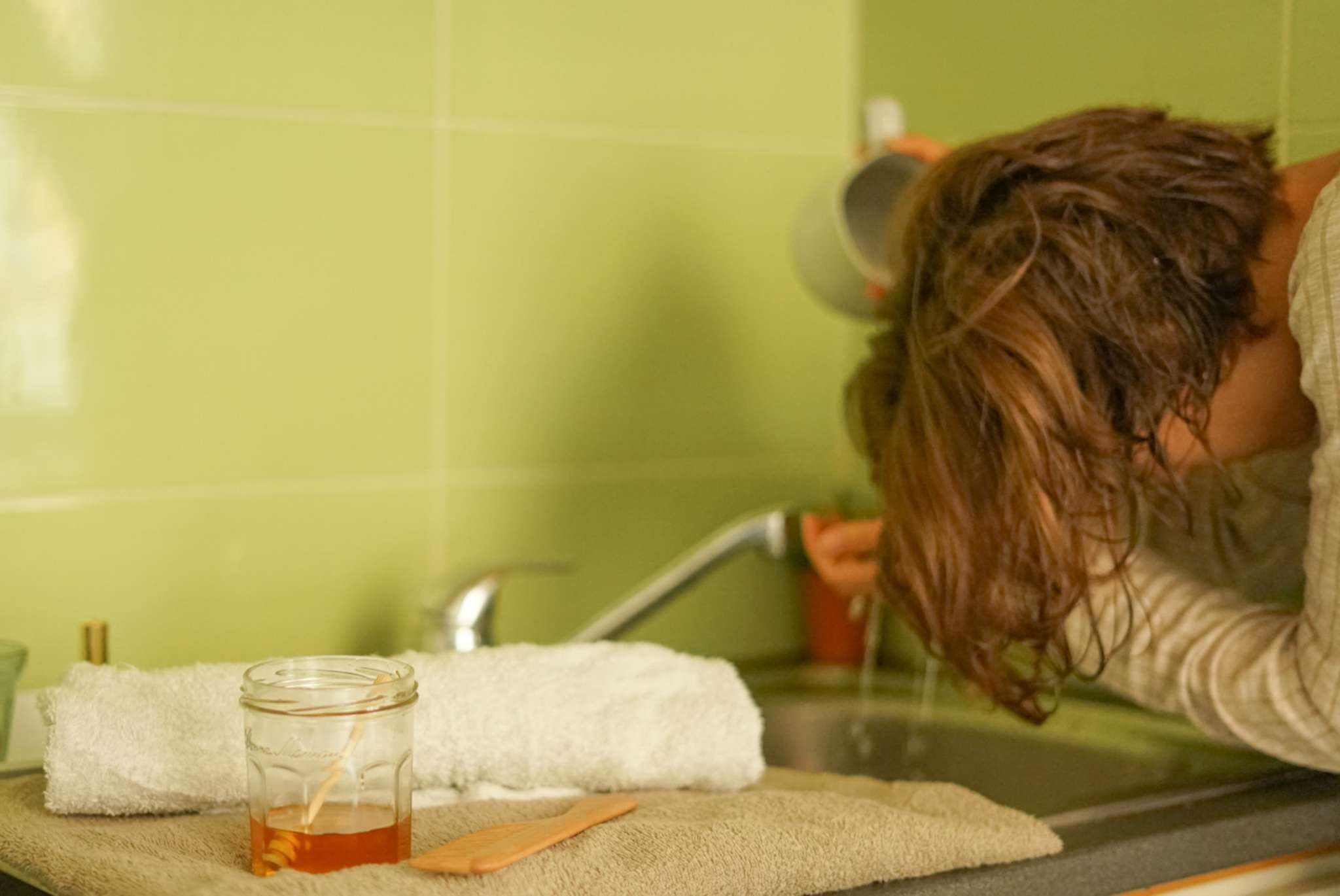 women bends overs kitchen sink and washes hair with honey