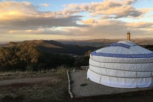 A yurt sits on a plateau overlooking a valley