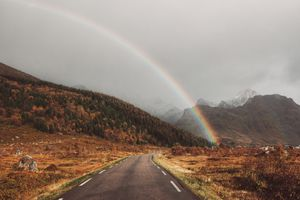 Rainbow over the road with mountains in the background