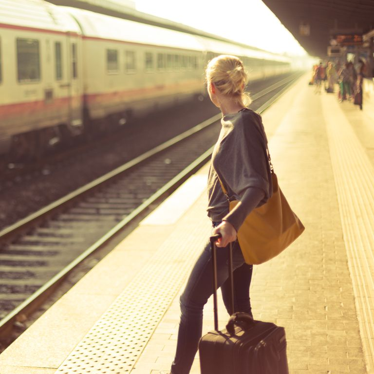 woman with suticase waits on platform for train