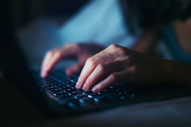 Close-up Shot Of Young Woman Working Late With Laptop In The Dark