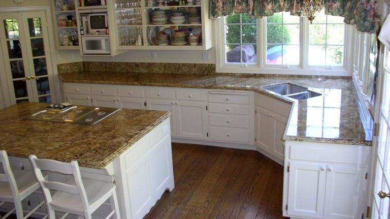 Kitchen with custom white cabinets and stone counters