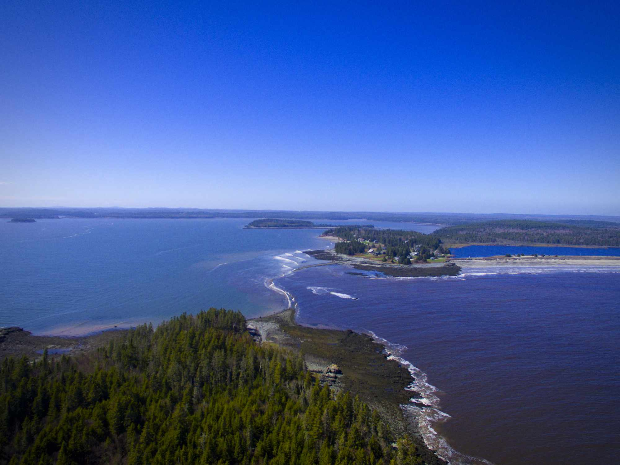 Aerial view of a clear blue sky and bright blue water of Roque Bluffs State Park and beach in Maine