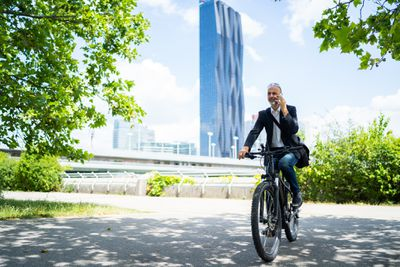 Man without helmet talking on phone while riding e-bike
