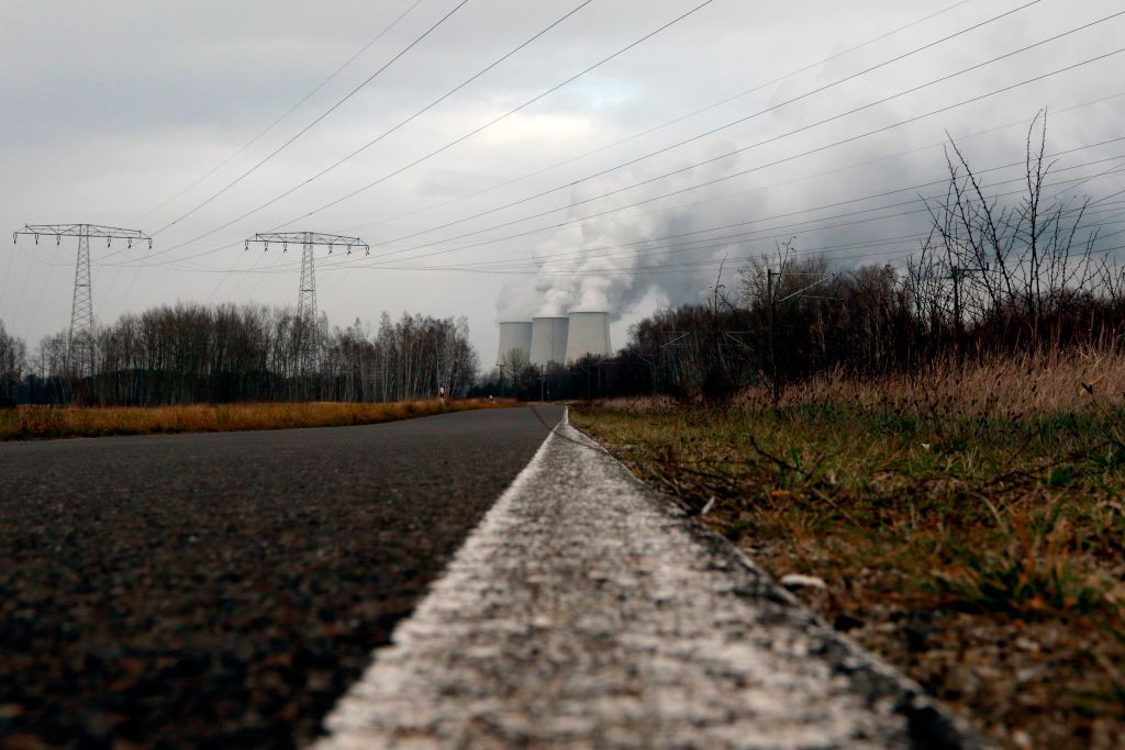 A road near the village of Peitz shows clouds of water vapor rising from the cooling towers of the Jaenschwalde lignite coal-fired power station in the Lusatian region in East Germany.
