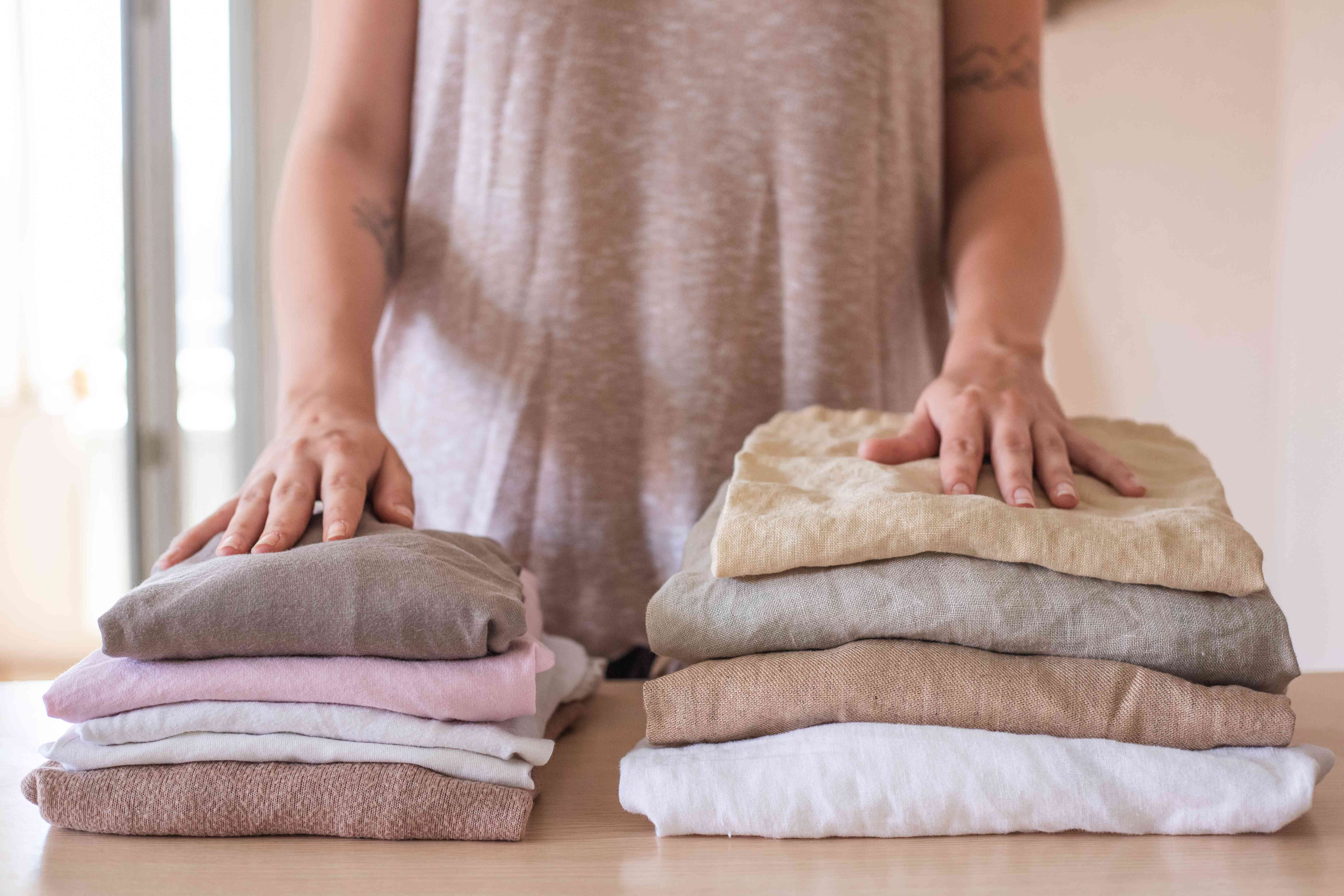 person stands in front of two folded piles of clothing: one cotton, one linen