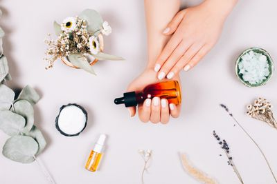 Hands holding bottle of oil surrounded by other beauty ingredients