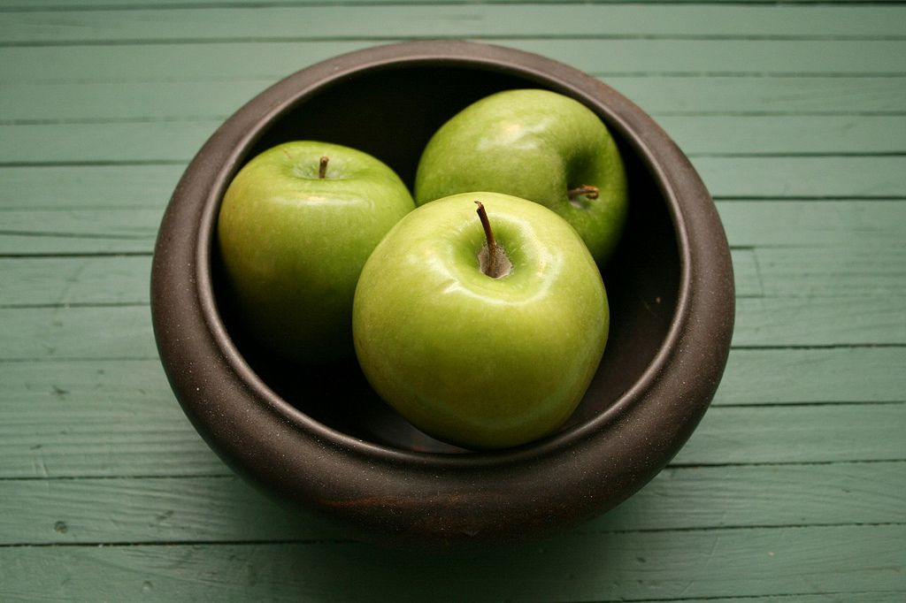 Bowl with three apples sitting on a wooden table