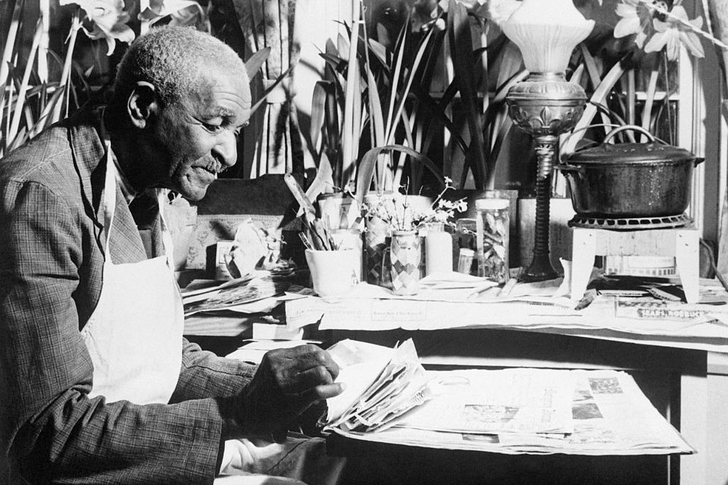 George Washington Carver working while surrounded by flowers