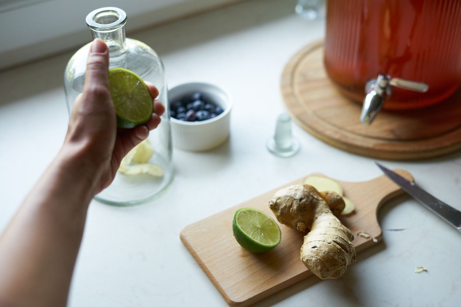 ginger, limes, and berries are on a cutting board to be added to homemade kombucha