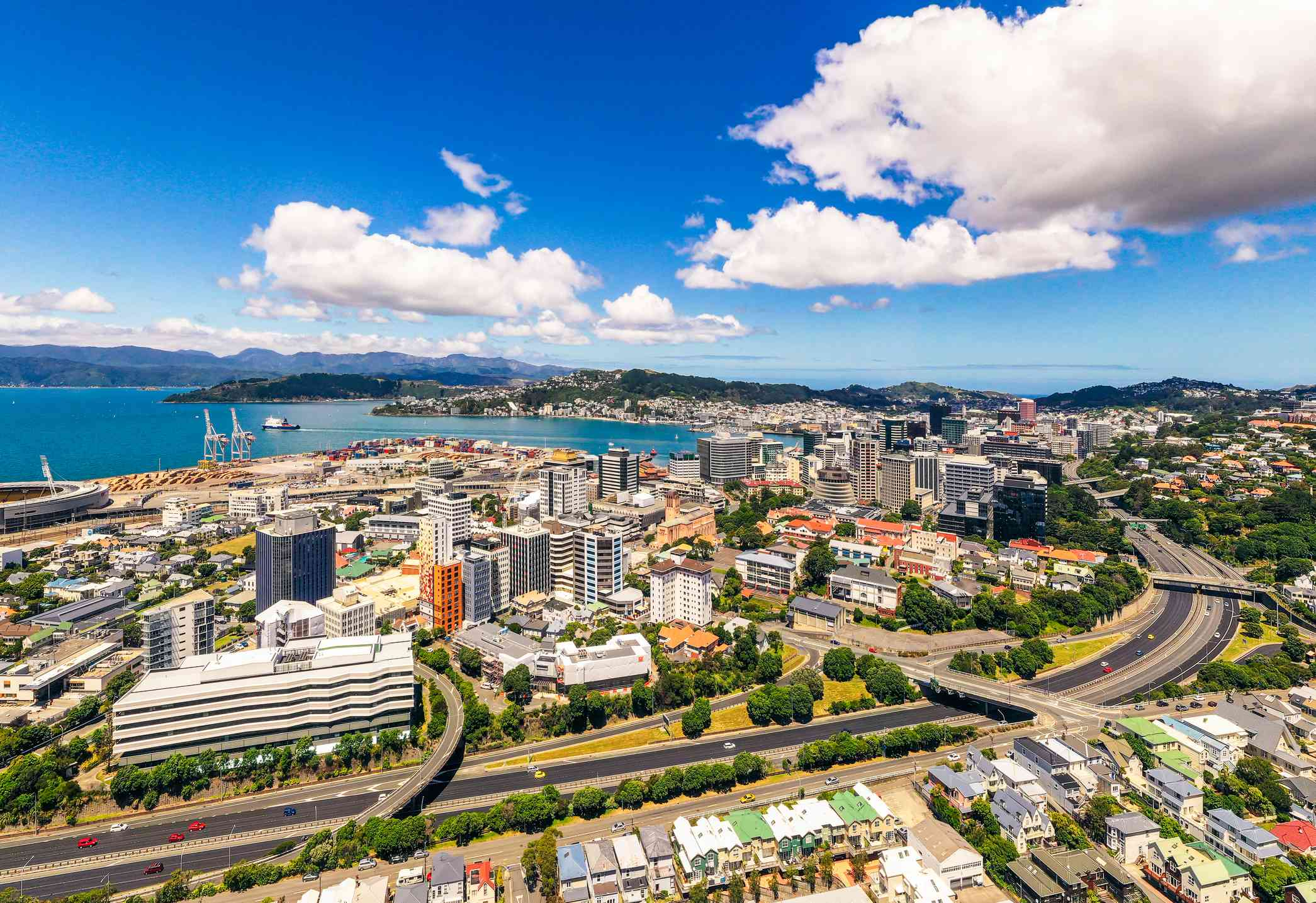 high angle view of Wellington with clean roads lined with trees in the foreground, followed by high rise buildings, and a bright blue river, with mountains in the background on a sunny day with a blue sky and white clouds