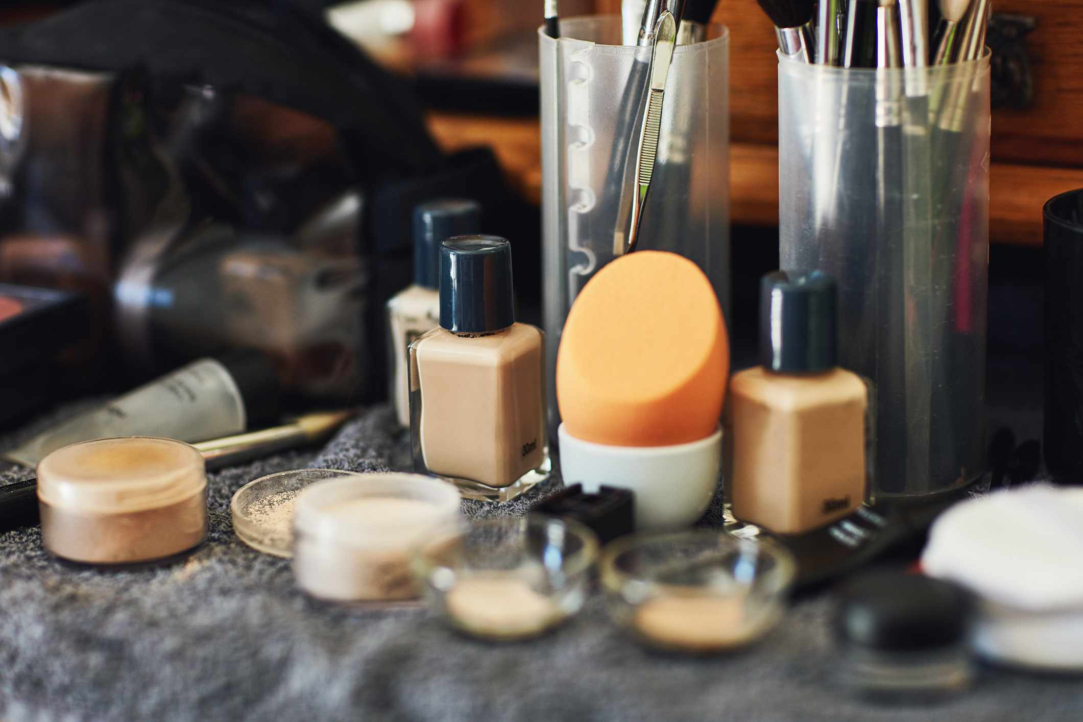 Make-up on a towel and in plastic containers and bags.