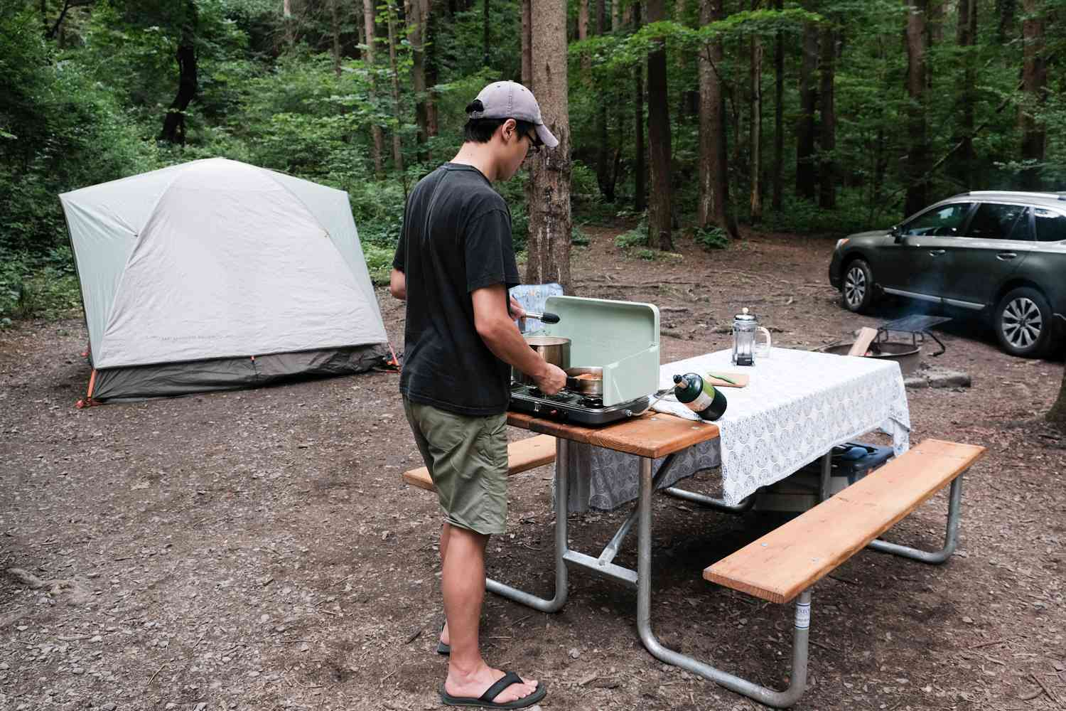 man cooks on camping stove on picnic table with tent and car nearby