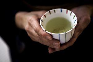 up close shot of hands holding green tea