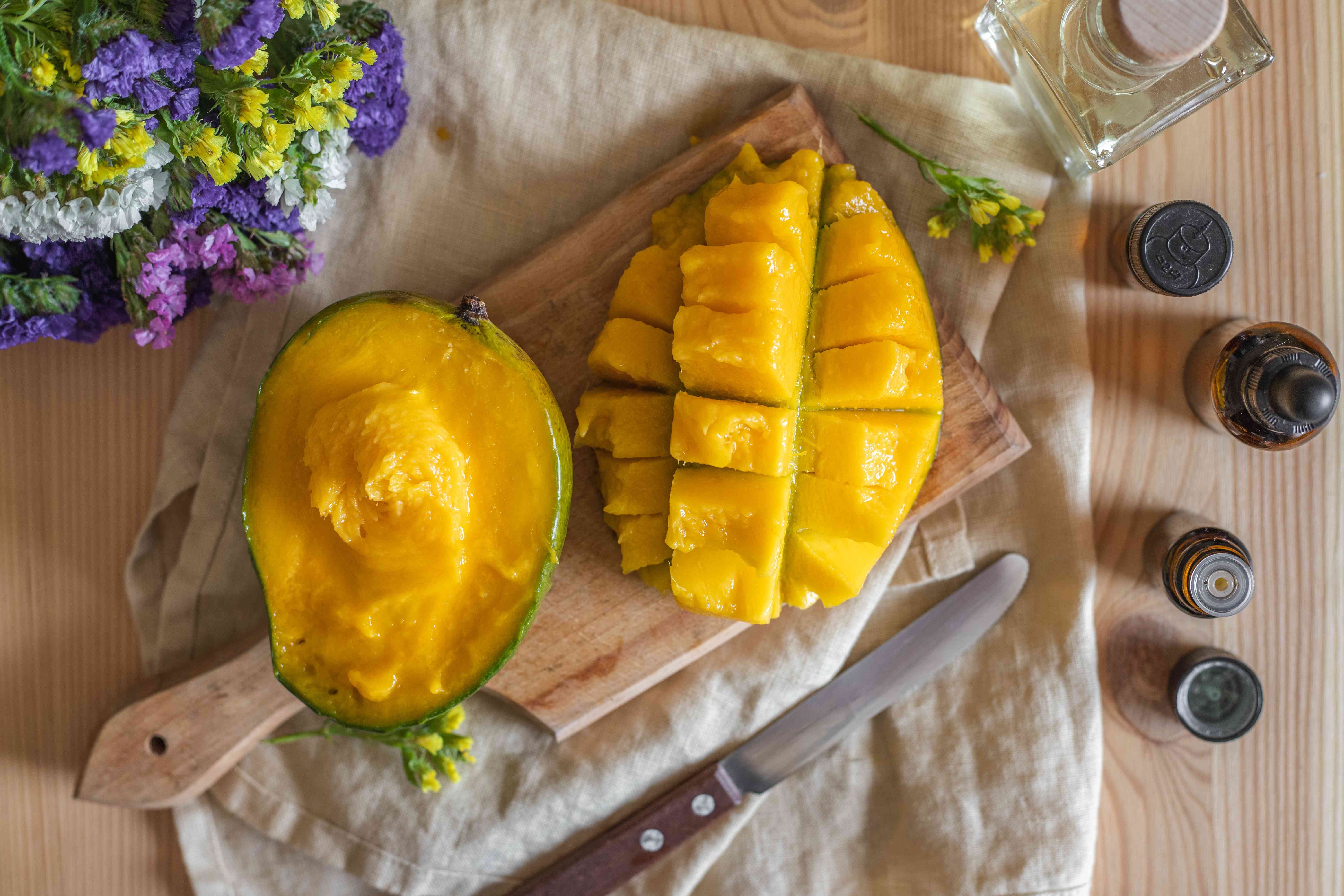 green mango cut in half with one side cubed on wooden cutting board next to fresh flowers