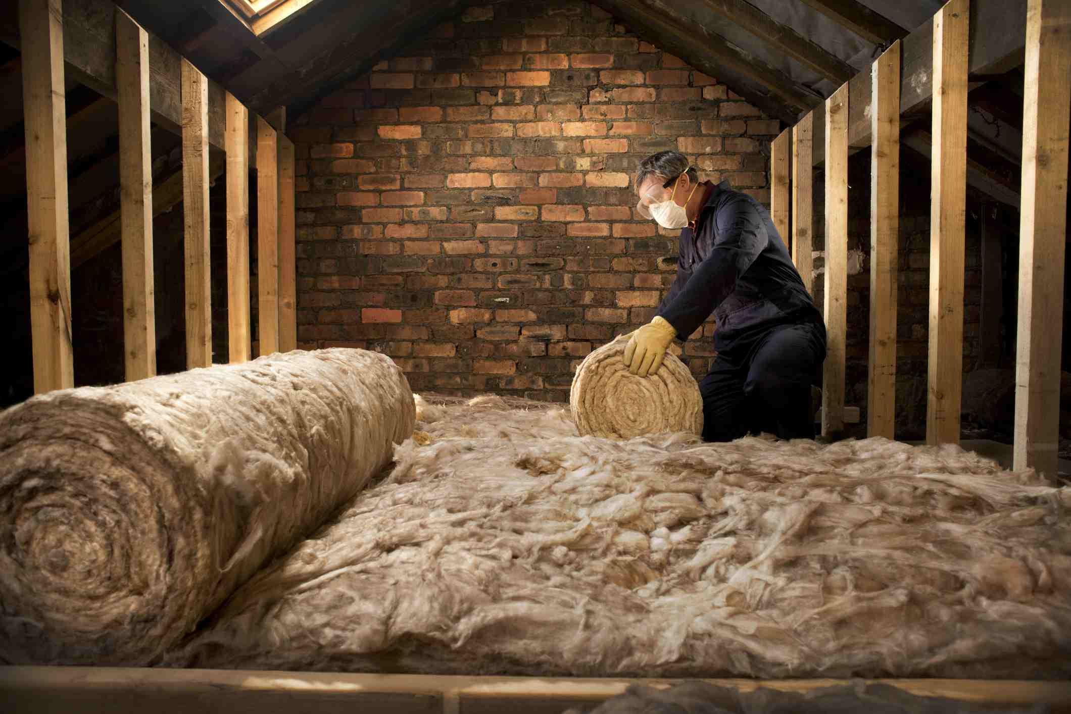 man puts insulation in his loft