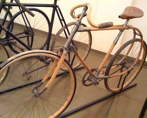 A wooden bike held up by a bike stand