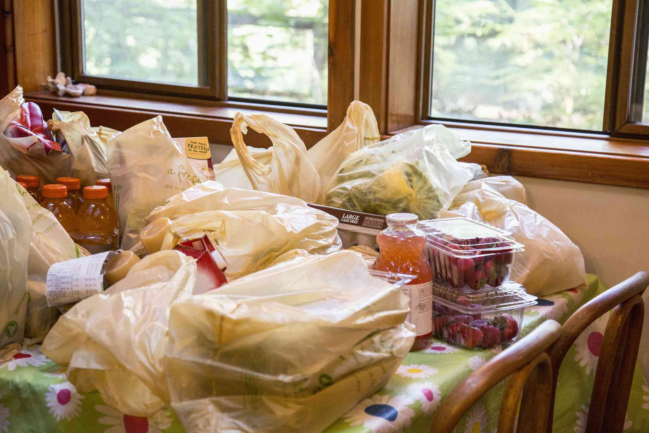 Bags of plastic holding groceries on a table.