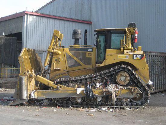 A bulldozer that runs over trash at a waste facility.