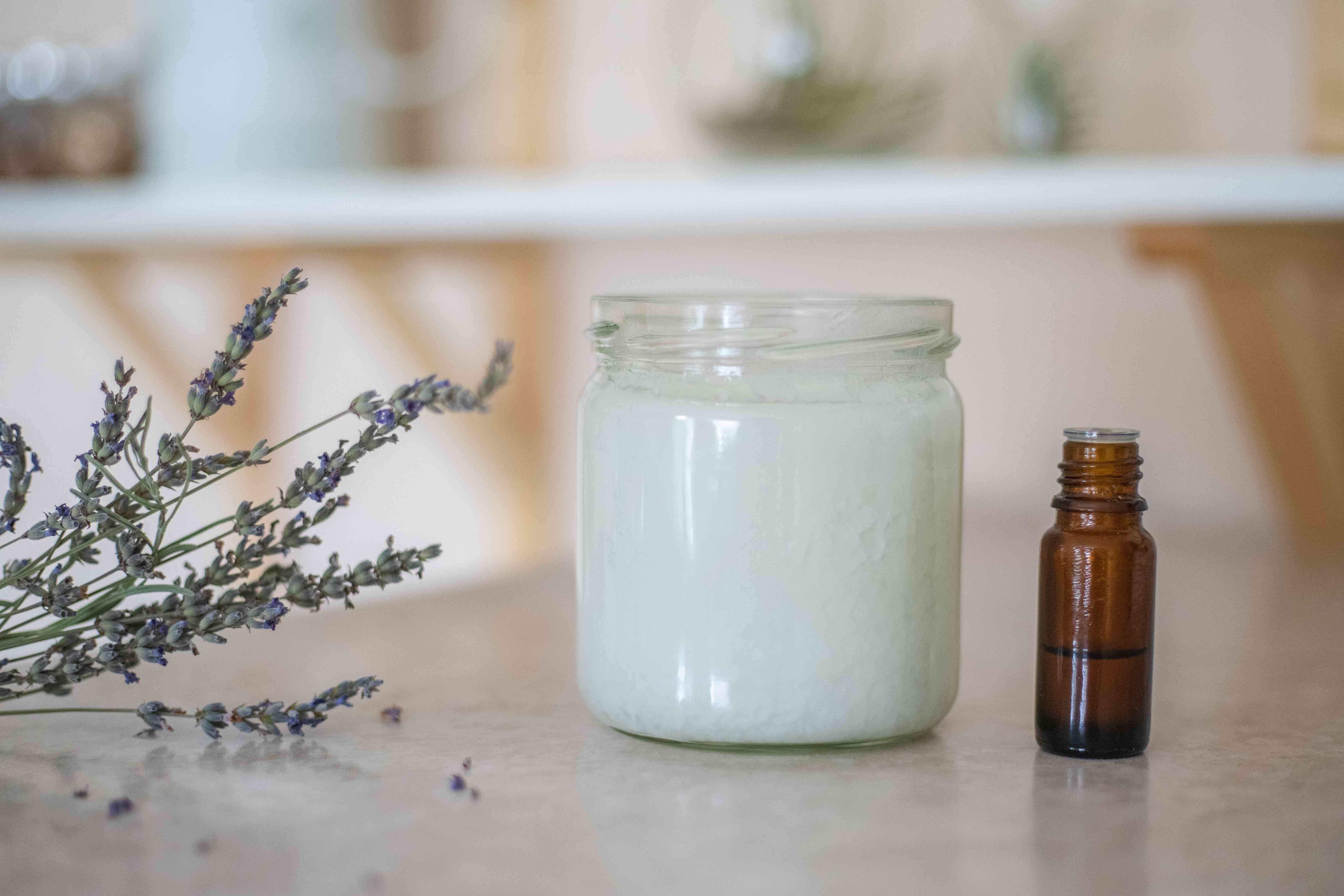a glass jar of coconut oil next to lavender essential oil and a sprig of dried lavender flowers