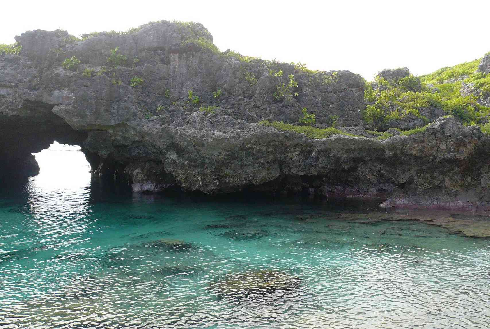 An arched rock formation extends over clear, tropical waters