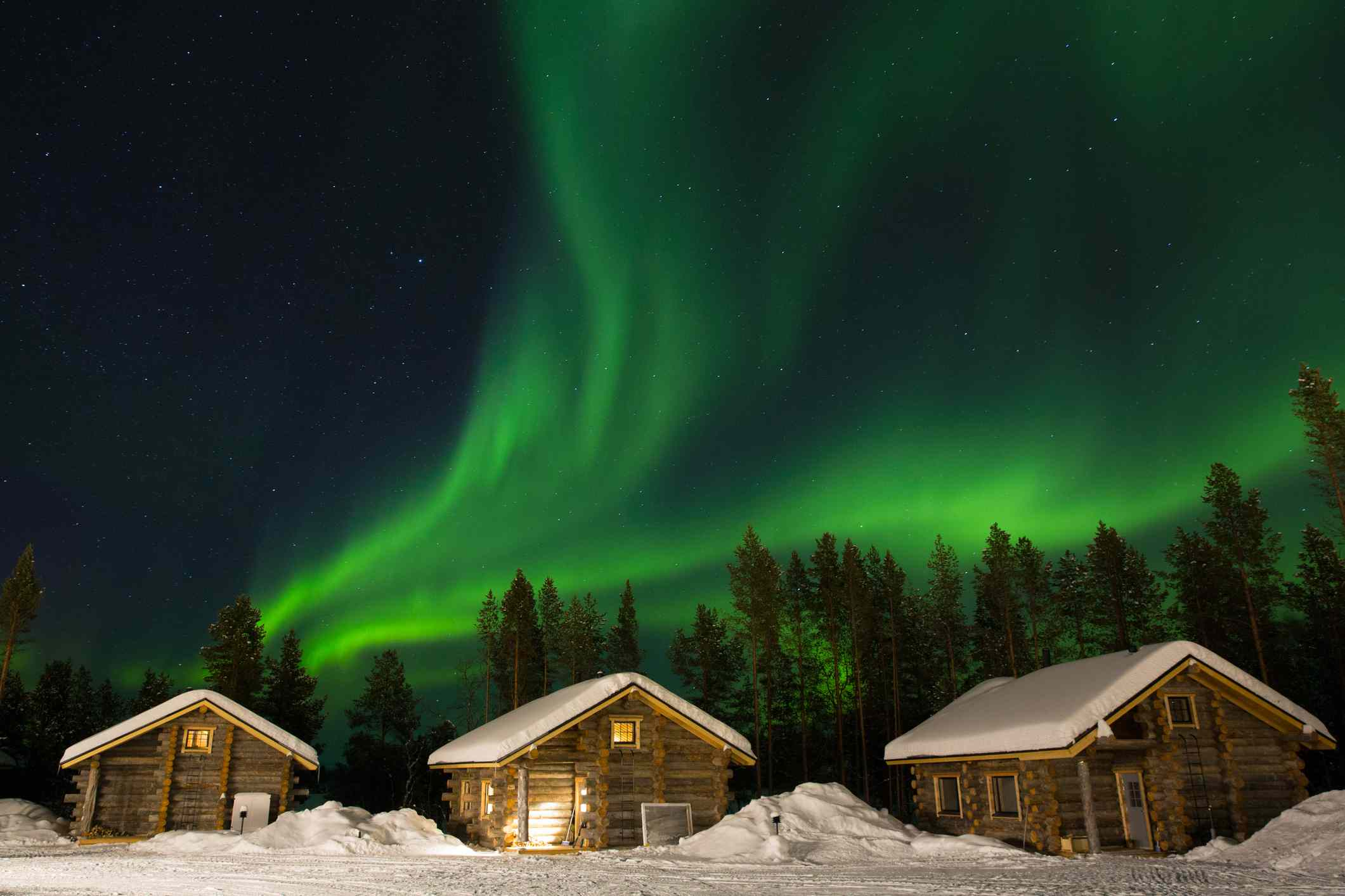 Green northern lights over snow-covered cabins in Laponia, Finland