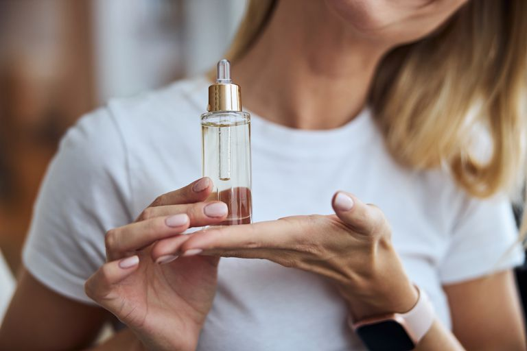 A white woman holds up elixir for her skin.