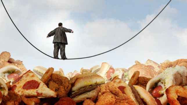 person on a highwire above fatty foods