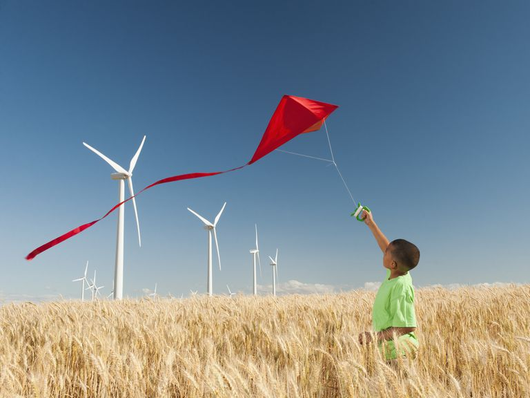 A young boy flies a kite in a field with wind turbines.