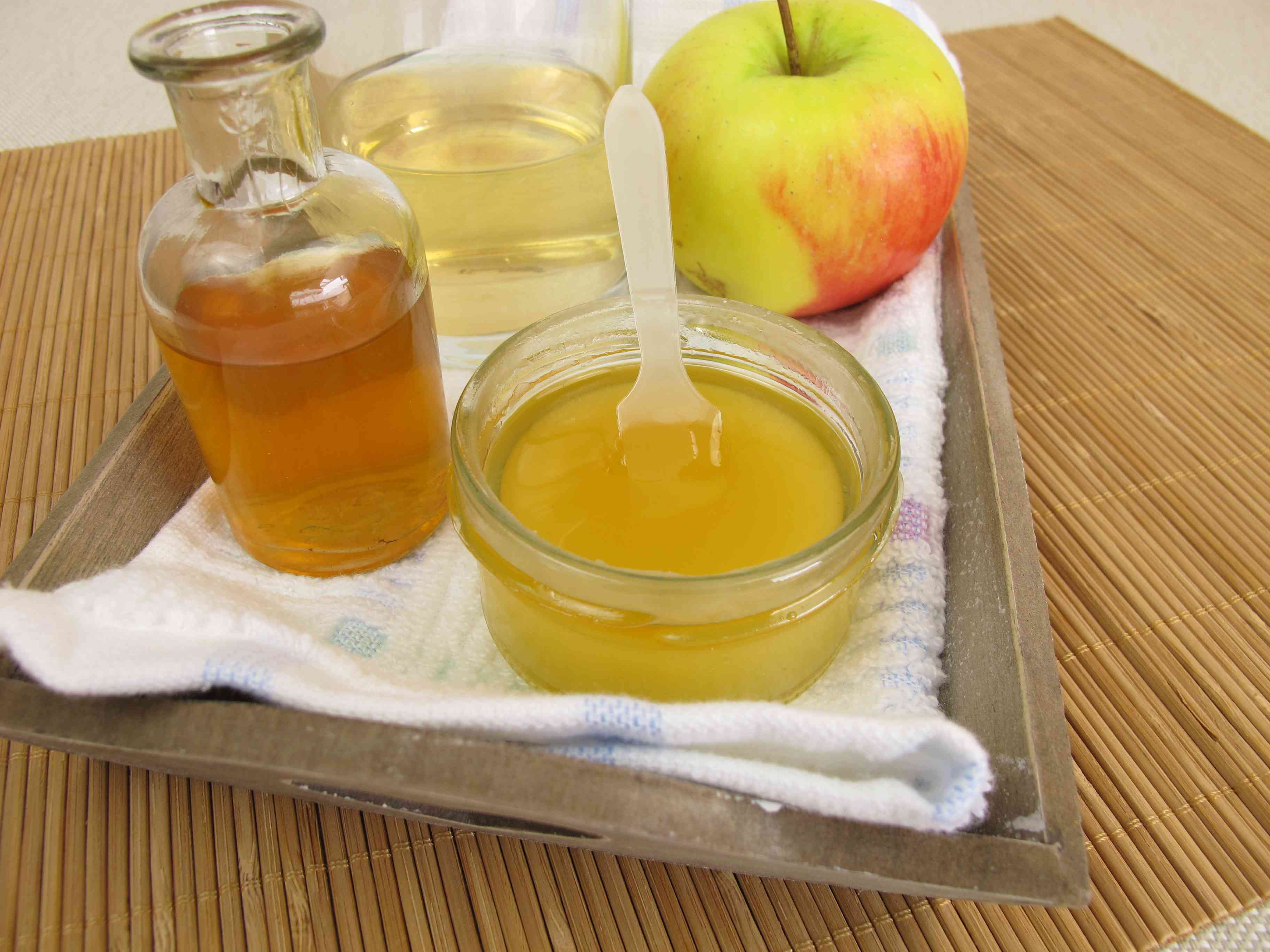 A bowl of apple cider vinegar mixed with water sits next to a bottle of apple cider vinegar and an apple in the background