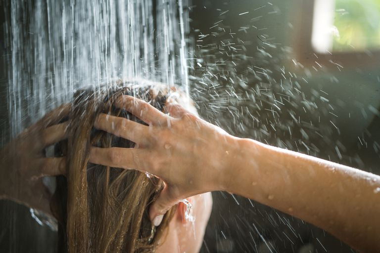 A woman washes her hair in a bathroom with natural light.