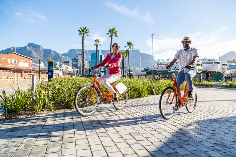 Couple riding rented bicycles in a city