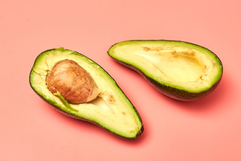 Sliced avocado on a pink background.