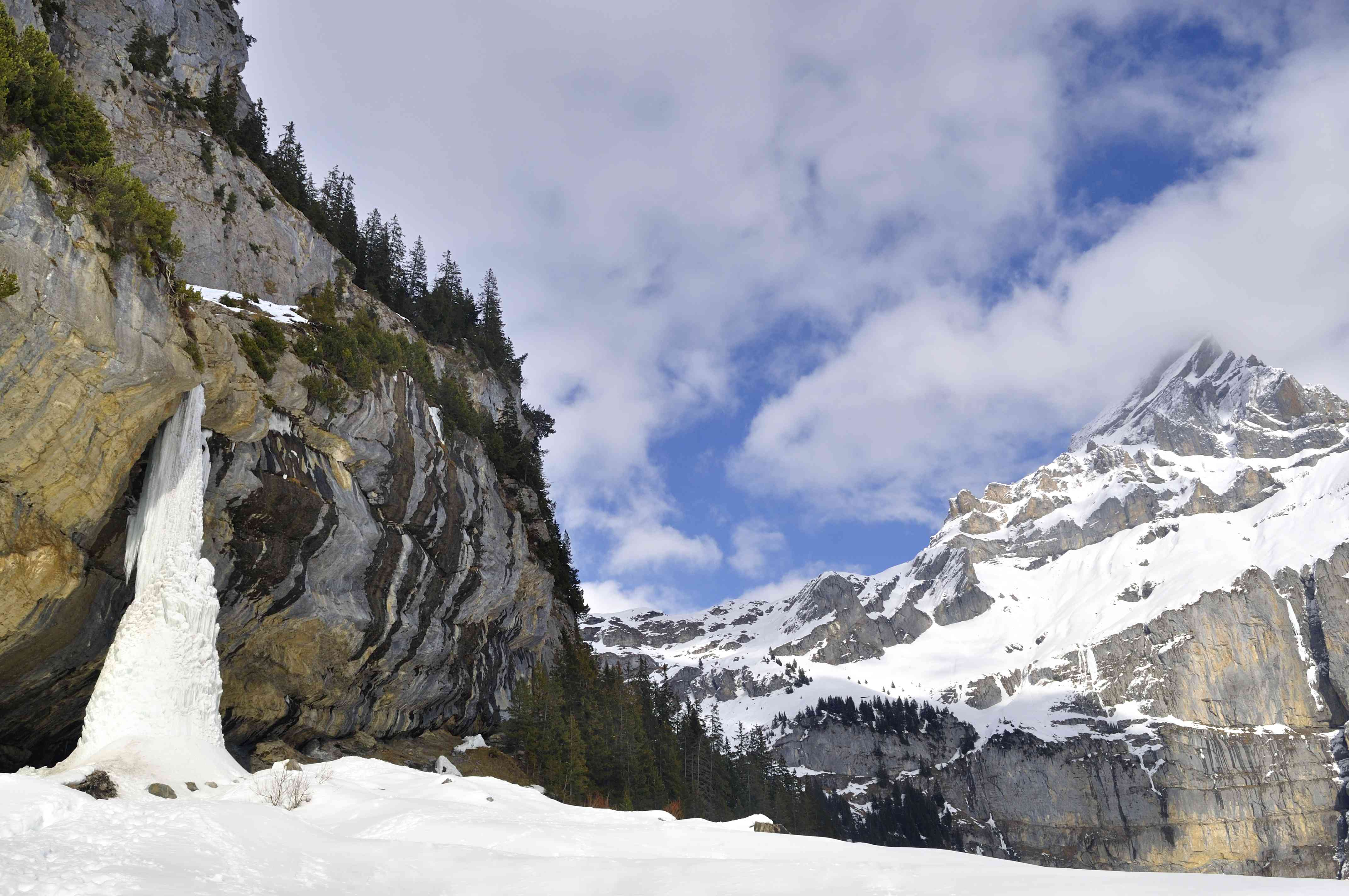 Frozen waterfall and mountains at Oeschiwald Lake