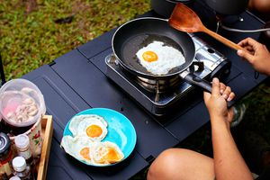 Person cooking sunnyside up eggs on a camp stove