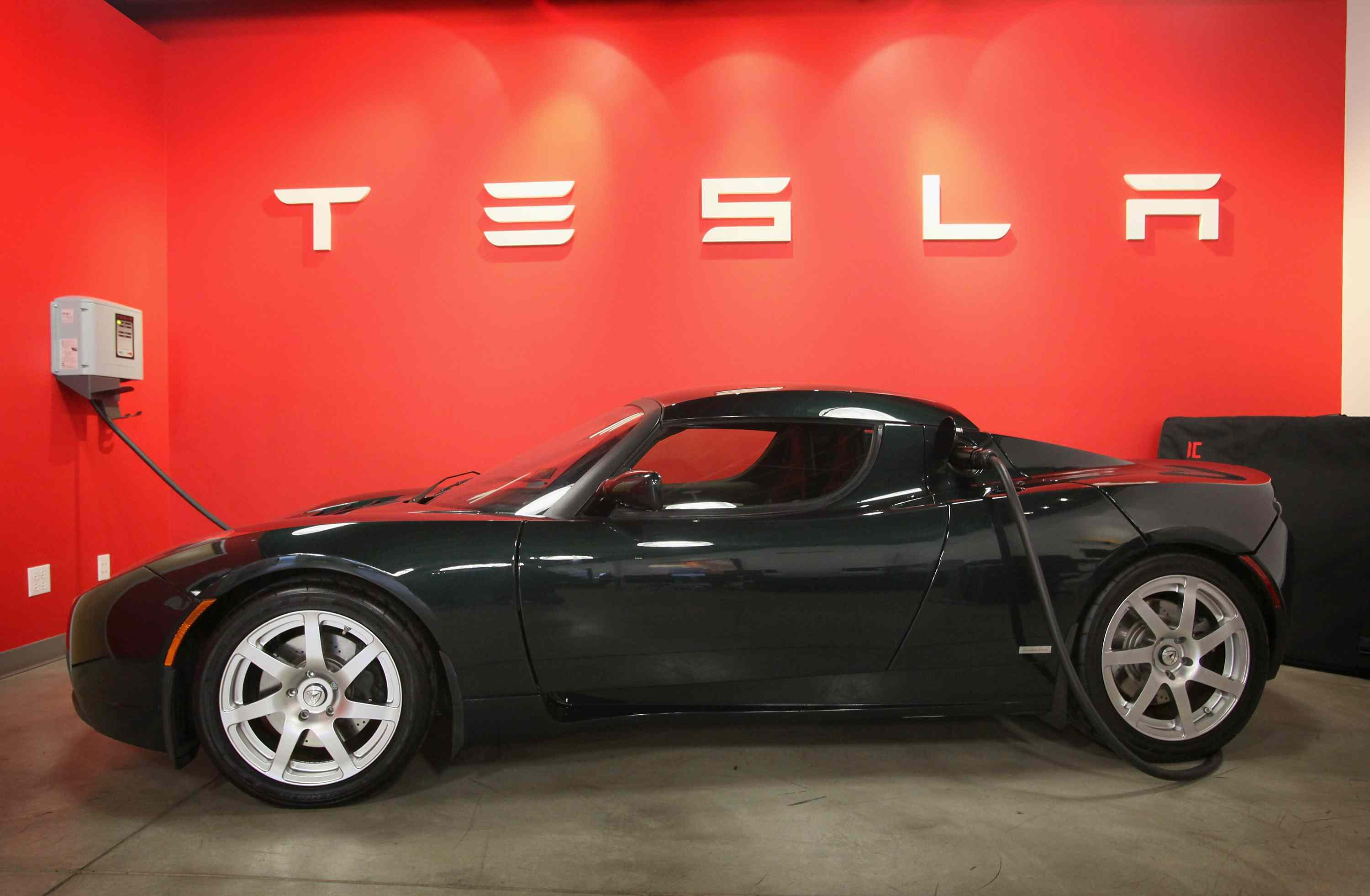 A Telsa Roadster in front of a red wall.