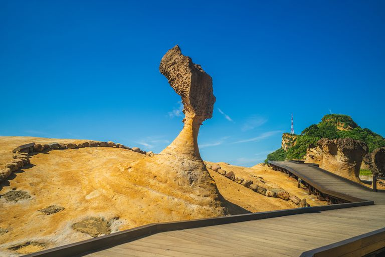 Queen's Head at Yehliu Geopark with a bright blue sky behind the carving and a wooden boardwalk below