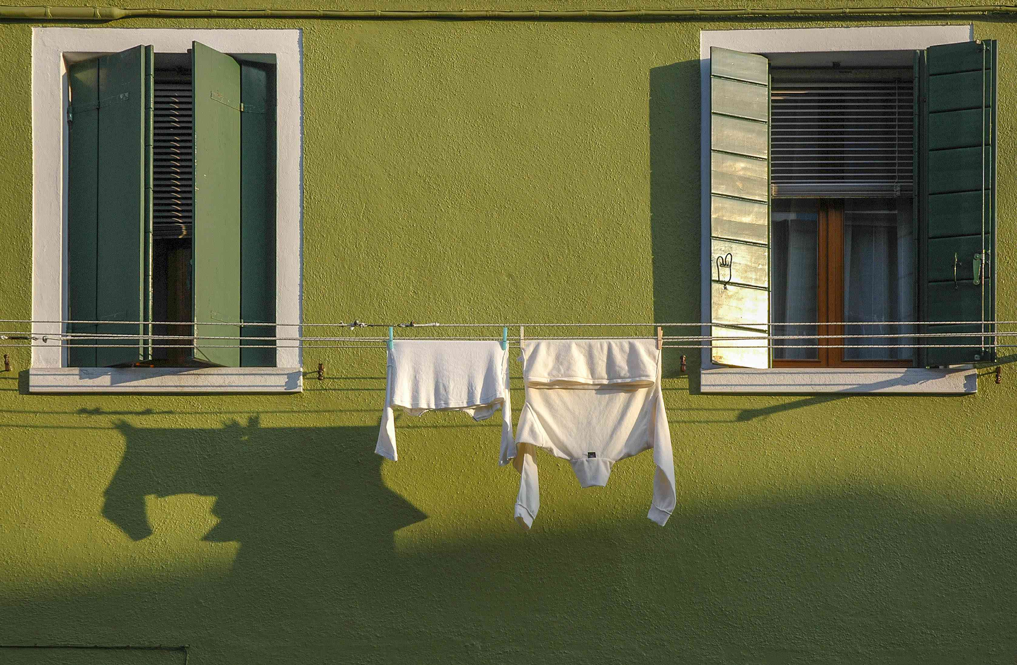Clothes dry in the sun on a clothesline strung between two windows.