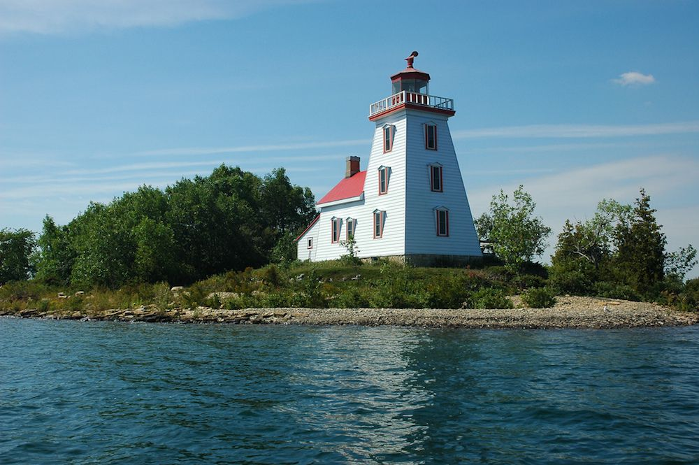 Strawberry Island Lighthouse under a blue sky surrounded by tall green trees and water on Manitoulin Island