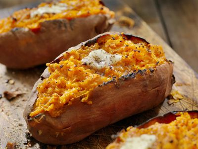 Twice baked sweet potatoes with melted butter and cracked black pepper sitting on a wooden board