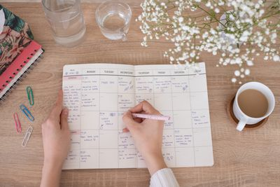 overhead shot of person writing in paper planner on desk with flowers and coffee