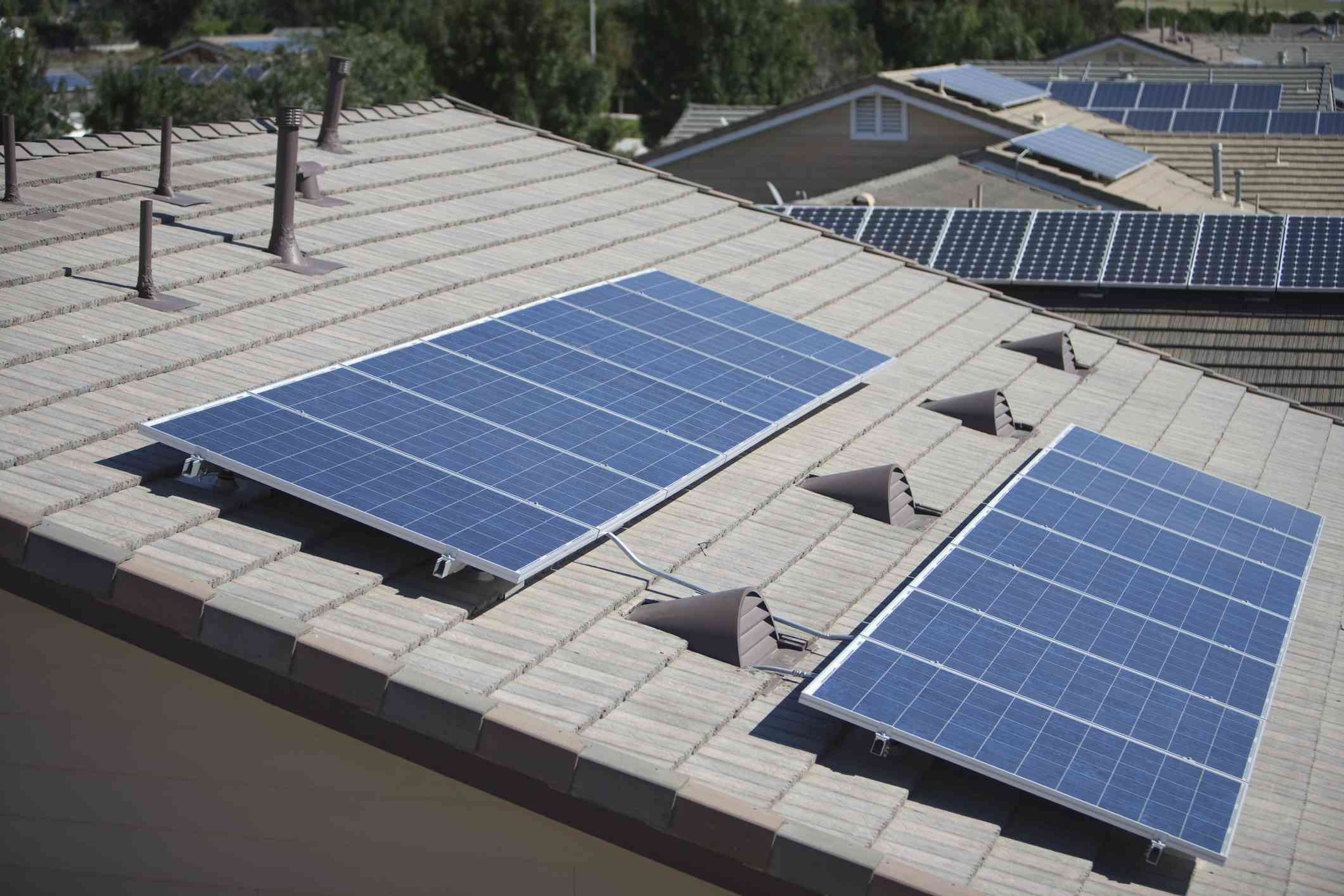 Solar panels on the roofs of various houses.