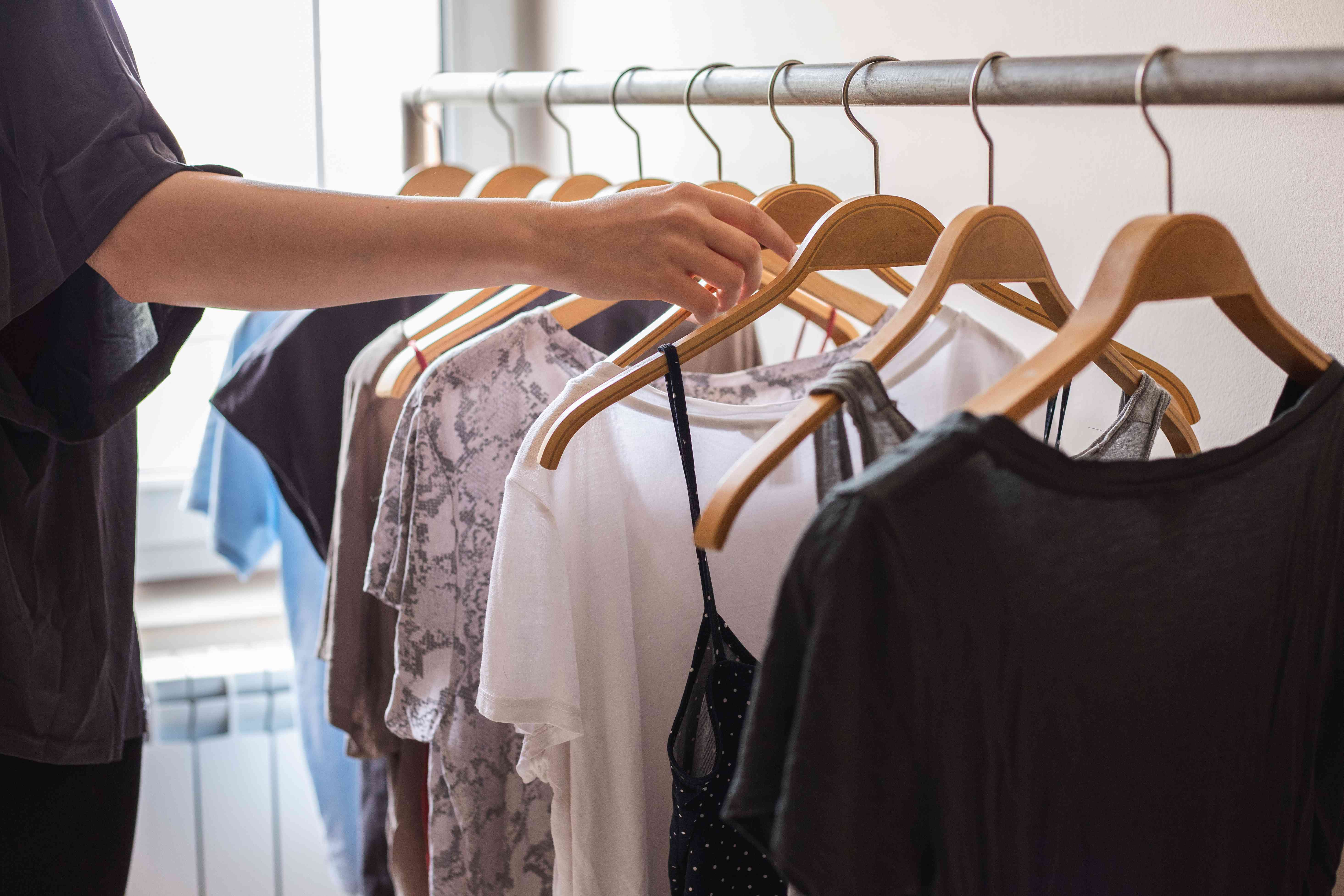 person's arm reaches for modal clothing hung up on wooden hangers on metal clothing rack