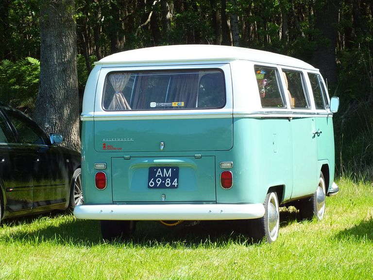 back view of a blue and white VW electric minibus parked on grass