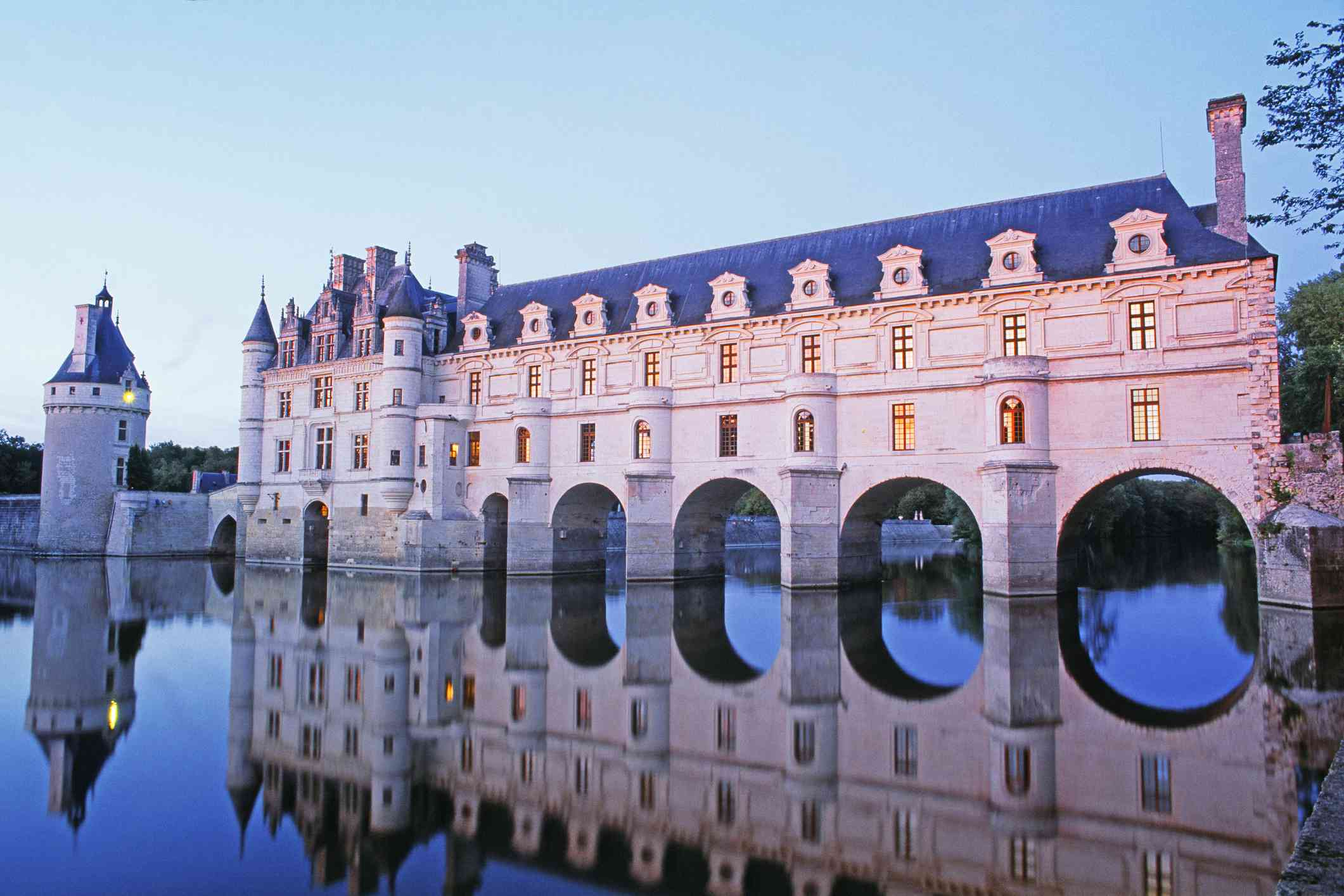 Château de Chenonceau on the River Cher under a clear blue sky at twilight